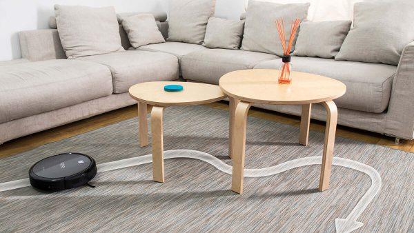 Robot aspirador conga limpia debajo de dos mesas salón